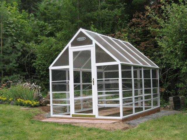 GlassHut greenhouse in backyard garden.